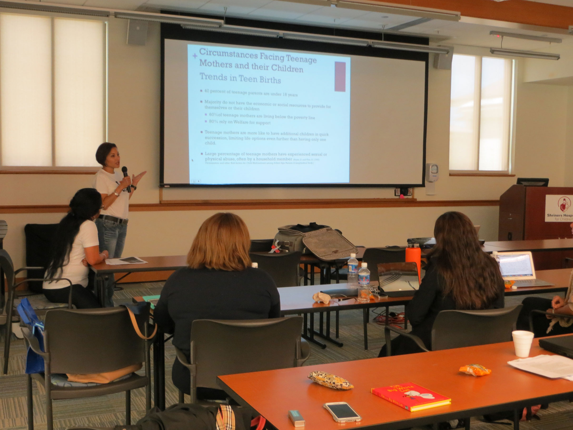 """Photo of LEND Trainees conducting a presentation while wearing """"I Love Guam"""" t-shirts."""