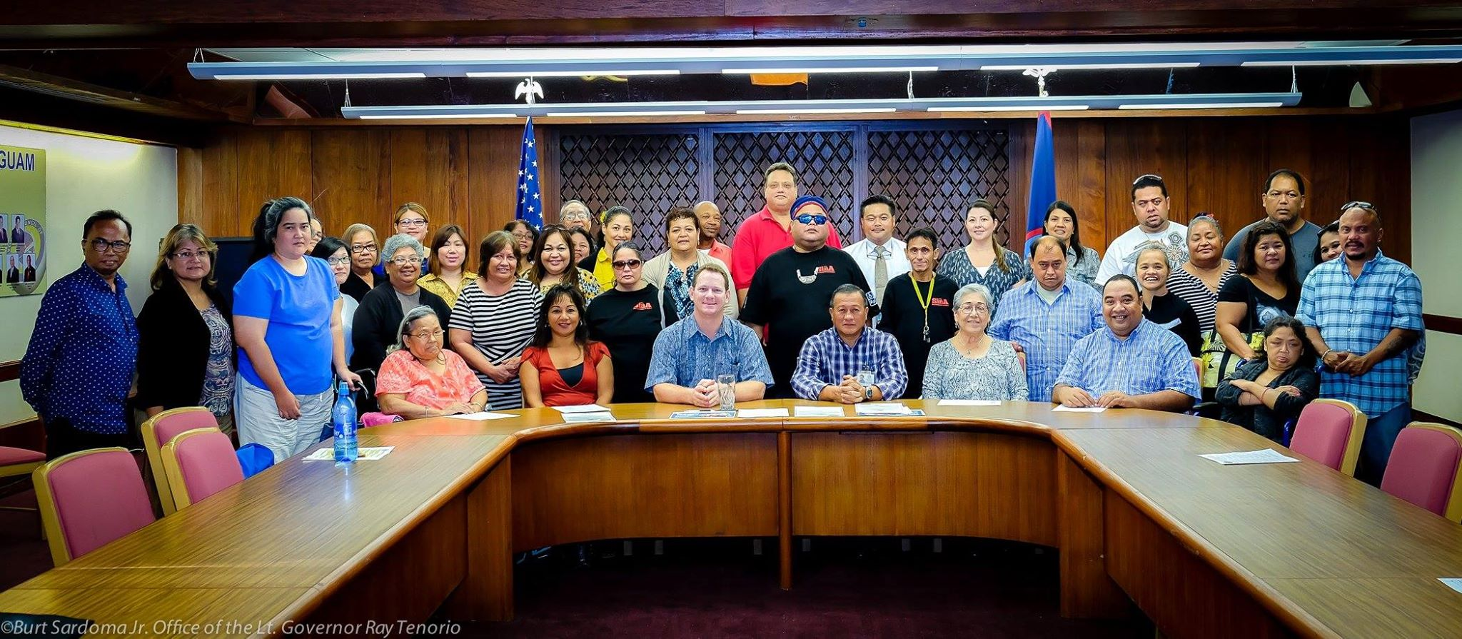 Large group poses for photo in Governor's conference room.