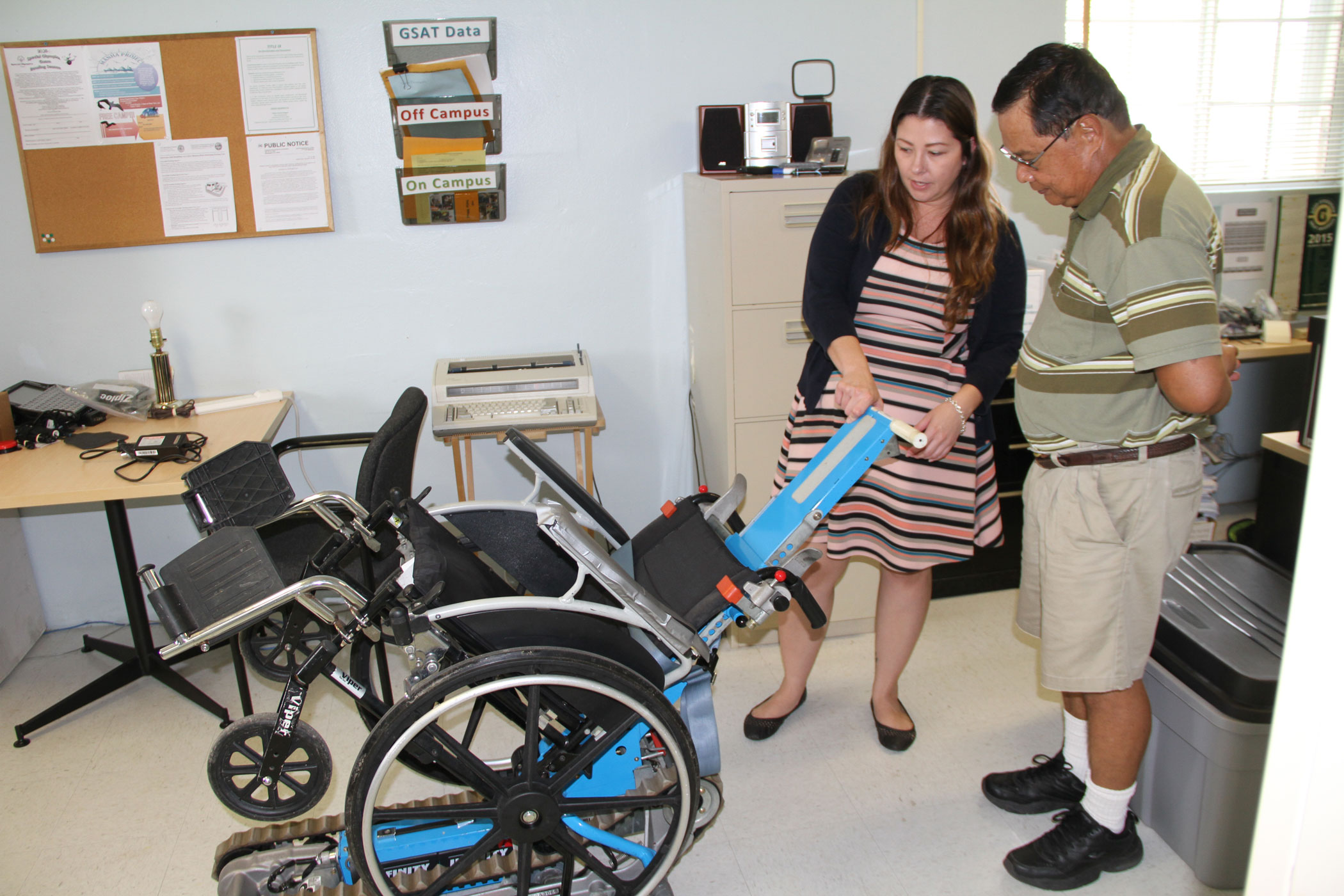 Two individuals looking at assistive technology device.