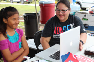 Vera Blaz (Right), Guam CEDDERS staff, takes a picture of a child for her Power of Play Passport on June 16 at Gill Baza, Yigo.