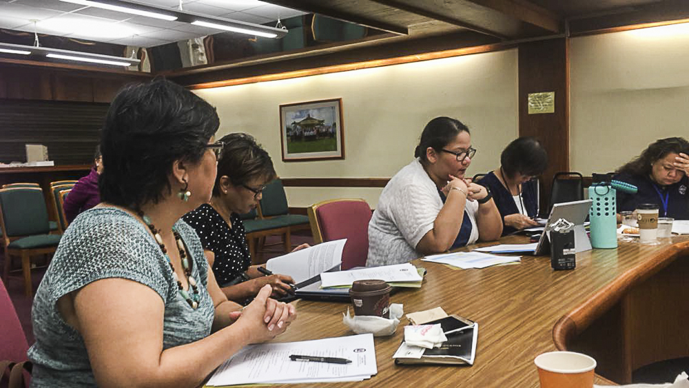 Vera Blaz, Project Tinituhon Project Coordinator (in white), talks about the islandwide Developmental and Behavioral Screening System (iDBSS) standard operating procedures for endorsement by council members during the Guam Early Learning Council quarterly meeting on November 1 at the Governor's Complex in Adelup.