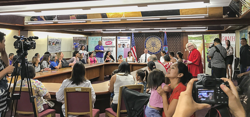 Attendees at the Breastfeeding Awareness Month Proclamation Signing gather around the table to witness the event.